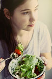 Teenager girl with cut cucumber tomato salad bowl royalty free stock photos