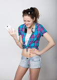 Teenager girl in denim shorts and a plaid shirt talking on mobile phone and express different emotions Royalty Free Stock Image