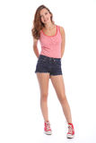 Teenager girl in denim shorts and vest happy smile. Pretty young teenager school girl 16, with long brown hair wearing blue denim cut off shorts and red and Stock Image