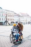 A teenager girl with disabled grandmother in wheelchair outdoors on the street in winter. royalty free stock photos