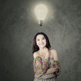 Teenager girl discover a solution. Thoughtful teenage girl smiling happy while looking up at bright lamp Royalty Free Stock Photos
