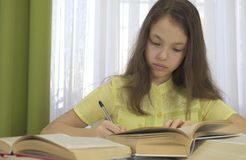 Teenager girl does homework at table. Teenager girl does homework at the table Royalty Free Stock Photography
