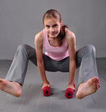 Teenager girl doing exercises with dumbbells to develop with dumbbells muscles on grey background. Full length portrait of teen ch Royalty Free Stock Photos