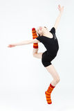 Teenager girl doing gymnastics dance in jumping on a white Stock Photos