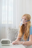 Teenager girl doing inhalation indoor Royalty Free Stock Photo