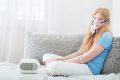 Teenager girl doing inhalation indoor Royalty Free Stock Images