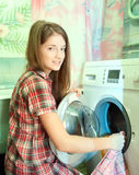 Teenager girl doing laundry. At her home Stock Photo