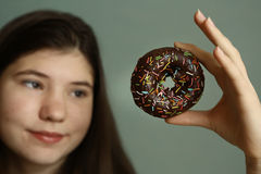Teenager girl with doughnut. Teen girl with doughnut close up photo Royalty Free Stock Image