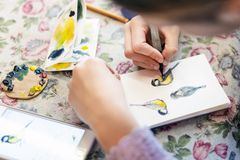 Teenager girl drawing bird in small paper drawing-pad. Close-up kid artist painting small picture on paper notepad with. Brush. Children creativity concept royalty free stock photos