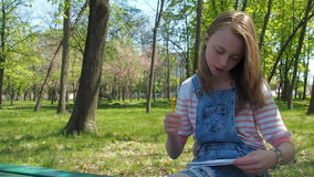 A teenager girl draws on nature. stock video