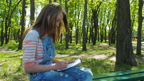 A teenager girl draws on nature. A girl in bracelets draws in the park. Hands of a teenager. stock footage