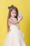 Teenager girl in a dress on a yellow background photographed themselves on the phone Stock Photography