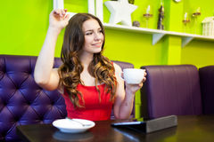 Teenager girl is drinking coffee in a cafe Royalty Free Stock Images