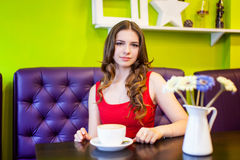 Teenager girl is drinking coffee in a cafe Stock Photos