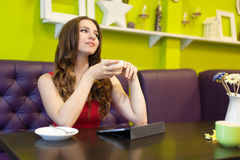 Teenager girl is drinking coffee in a cafe Royalty Free Stock Photography