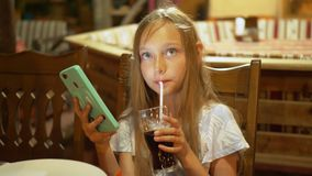 Teenager girl drinking from glass fizzy water and looking smartphone. Young girl drinking soda using mobile phone stock footage