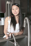 Teenager girl drinking water in the kitchen Stock Photography