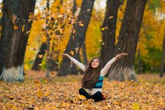 Teenager girl drop up leaves in autumn park. Happy little girl in autumn park throws up fallen maple leaves Royalty Free Stock Image