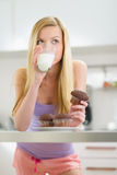 Teenager girl eating chocolate muffin with milk Royalty Free Stock Photos