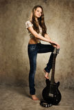 Teenager girl with electric guitar. Barefooted teenager girl with electric guitar against wall background Royalty Free Stock Images