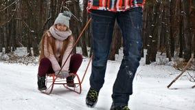 Teenager girl enjoying sleigh ride. Boy pulling sled - slow motion stock footage