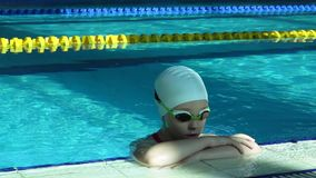 Teenager girl face in swimming pool. Close up of woman portrait smiling in resort pool water. stock footage