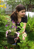 Teenager girl with flowers on pot gardening stock image
