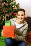 Teenager girl with gift boxes. Christmas three behind her Royalty Free Stock Photos