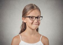 Teenager girl with glasses looking suspicious, skeptical Royalty Free Stock Images