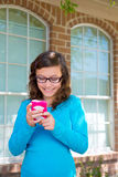 Teenager girl with glasses playing with smartphone Stock Photos