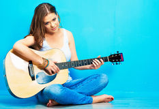 Teenager girl guitar play. Long haired girl sitting on a floor with crossed legs Royalty Free Stock Photo