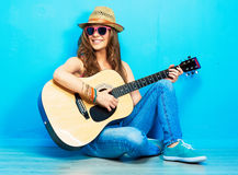 Teenager girl guitar play sitting on a floor. Blue wall  background. Country style Stock Photo