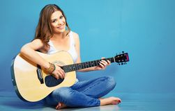 Teenager girl guitar play. Long haired girl sitting on a floor with crossed legs Royalty Free Stock Photography