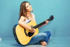 Teenager girl guitar play. Long haired girl sitting on a floor with crossed legs Royalty Free Stock Images