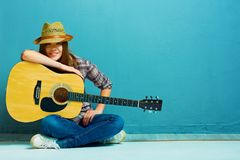 Teenager girl guitar play. Teenager girl guitar play sitting on a floor. Blue background. Country style Royalty Free Stock Photo