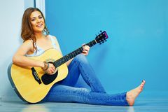 Teenager girl guitar play. Young model with long hair sitting on a floor Stock Photo