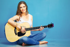 Teenager girl guitar play. Young model with long hair sitting on a floor Stock Image