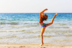Teenager girl during gymnastic workout on the beach. In the afternoon Royalty Free Stock Photography