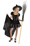 Teenager girl in Halloween witch with broom Royalty Free Stock Photo