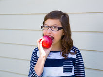 Teenager girl happy eating an apple royalty free stock photography