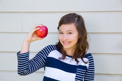 Teenager girl happy eating an apple Royalty Free Stock Image
