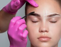 Teenager girl having eyebrow dyeing. The make-up artist painted one of her eyebrows. Professional makeup and skin care