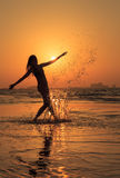 Teenager girl having fun during sunset. Girl enjoying active workout during sunset doing funny splash in the shore water. Water splash looks like golden drops in Royalty Free Stock Photos