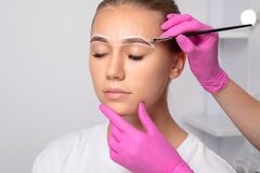 Teenager girl having permanent makeup tattoo on her eyebrows. Make-up artist makes markings with white paste for eyebrow tattooing