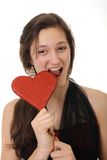 Teenager girl and heart. Teenager girl biting a red heart on a white background Stock Photo
