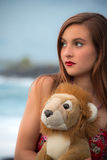 Teenager girl with her lion plush toy. Teenager girl holds her plush lion looking to future sad for losing childhood Stock Photo