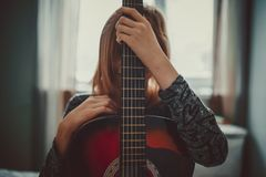Teenager girl hiding behind guitar. With window backlight Stock Photo