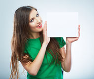 Teenager girl hold white blank paper. Young smiling woman show Royalty Free Stock Images