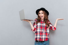 Teenager girl holding laptop and copyspace on her palms Stock Image