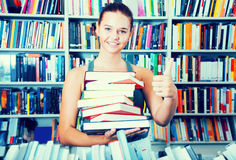 Teenager girl holding a stack of books in bookstore Stock Photos